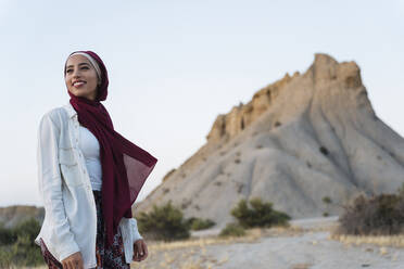 Smiling young tourist woman wearing Hijab in desert landscape - MPPF00992