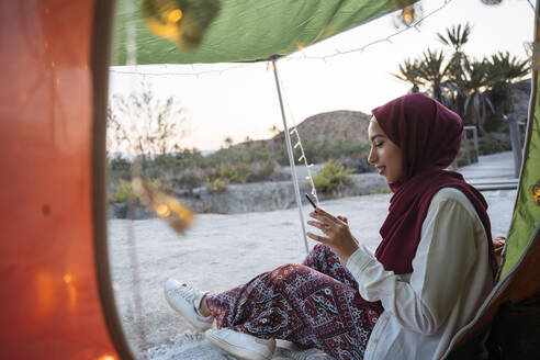 Young tourist woman wearing Hijab at a tent using mobile phone - MPPF00998