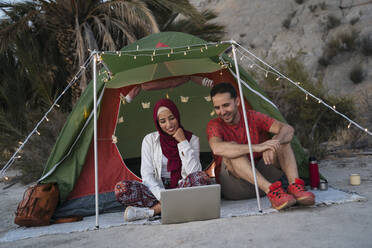 Young woman wearing Hijab and man using laptop at a tent - MPPF01001