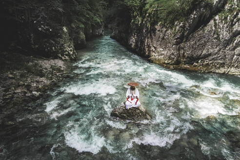 European yamabushi monk sitting on rock in the middle of river and meditating - HMEF01054