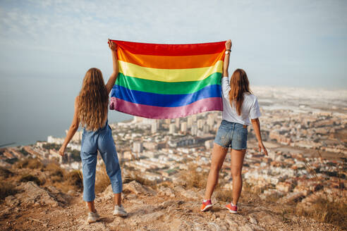 Two young women with an LGBT flag above the coastal city of Almeria, Spain - MIMFF00129