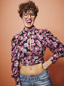 Beautiful curly haired female in trendy eyeglasses and stylish colorful blouse with floral ornament looking at camera and making funny grimace with tongue out standing against pink background - ADSF09204
