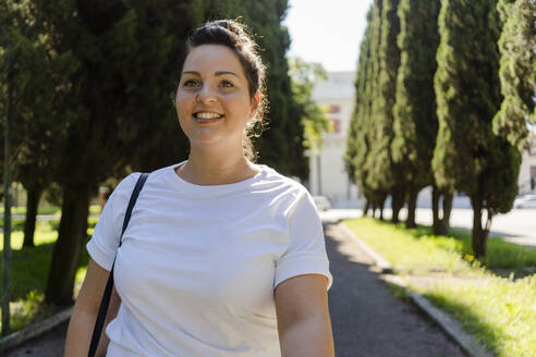 Smiling curvy young woman in a public park - GIOF08621