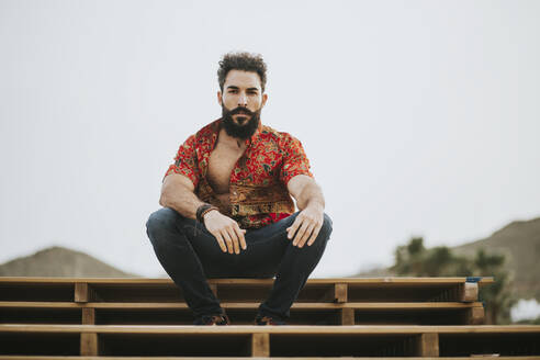 Attractive bearded man with colorful shirt sitting on wood stack - MIMFF00149