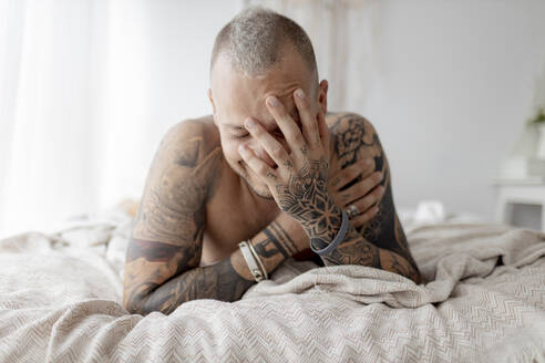 Tattoed hipster with hand on face lying on bed at home - GMLF00411
