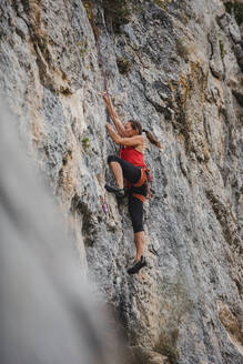 Determined woman climbing rocky mountain - DMGF00111
