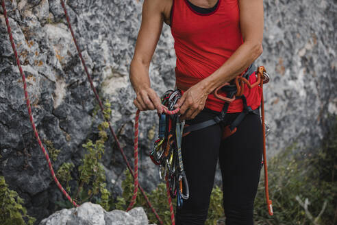 Woman adjusting ropes while preparing for rock climbing - DMGF00114