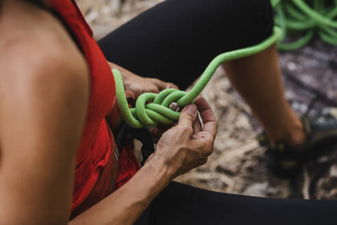 Female climber adjusting ropes while preparing for rock climbing - DMGF00117