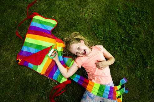 Happy girl holding colorful kite while lying down in park - IHF00379