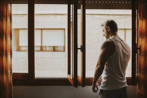 Thoughtful mid adult man looking through window while standing at home - MIMFF00159