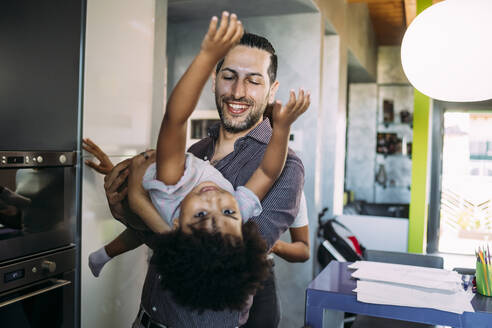 Smiling father carrying playful daughter while standing at home - MEUF01886