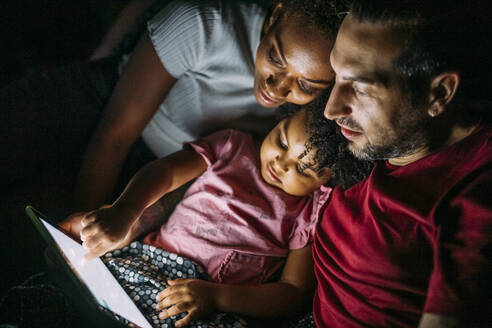 Parents with daughter using digital tablet while relaxing on bed at home - MEUF01922