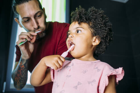 Close-up of daughter with father brushing teeth in bathroom at home - MEUF01925