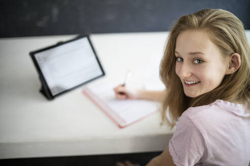 Blond girl learning and using tablet at home - DKOF00033