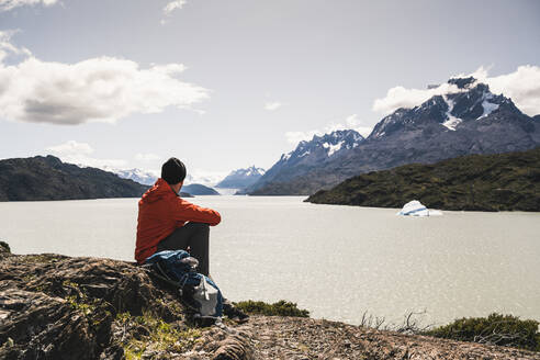 Man looking at river while sitting at Torres Del Paine National Park, Patagonia, Chile, South America - UUF20825