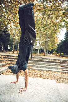 Young man doing handstand in public park during autumn season - EHF00746