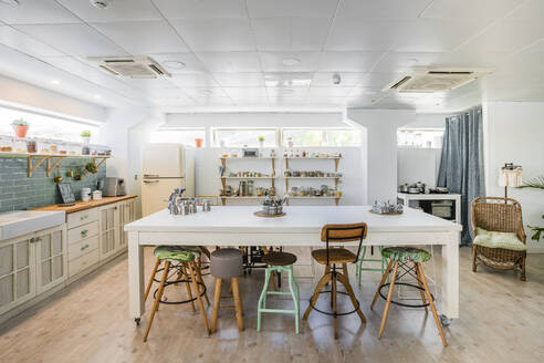 Seats arranged at kitchen island in cooking school - DLTSF00983