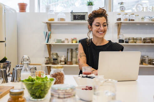Smiling woman using laptop on kitchen island at cooking school - DLTSF01010