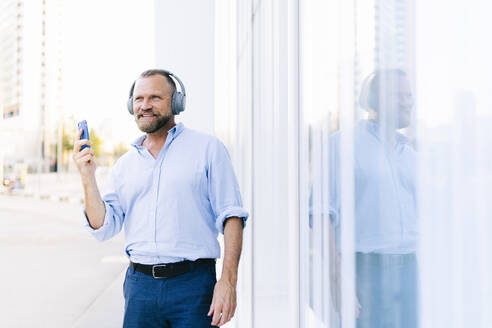 Businessman holding smart phone while listening music in city - DGOF01228