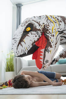 Shirtless boy sleeping by large toy dinosaur on carpet at home - SNF00461