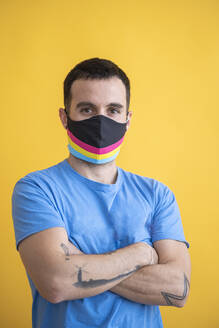 Close-up of man wearing multi colored mask with arms crossed standing against yellow background - SNF00476
