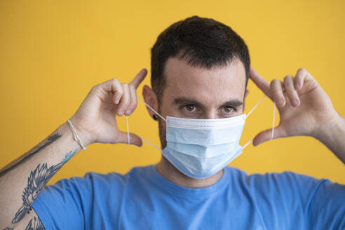 Close-up of man wearing mask looking away against yellow background - SNF00479