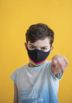 Close-up of boy wearing multi colored mask pointing while standing against yellow background - SNF00485
