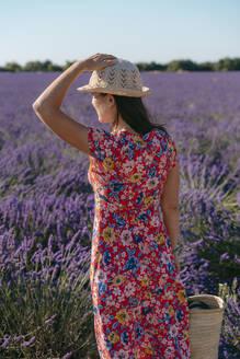 Woman wearing floral dress standing in vast lavender field - GEMF03973