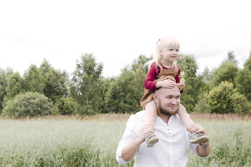 Father carrying daughter on shoulders while standing in oats field against clear sky - EYAF01244
