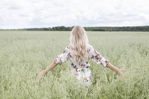 Young woman with blond hair standing amidst oats field against cloudy sky - EYAF01247