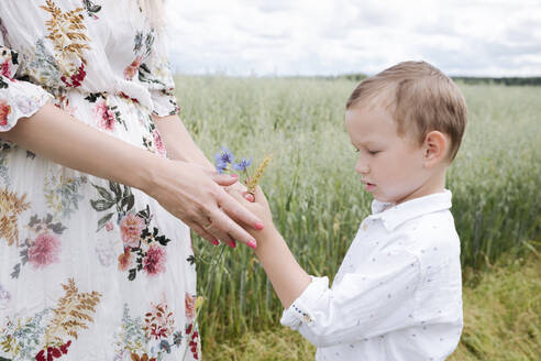 Russia, Ryazan, mother's hands giving flowers to her little son - EYAF01259