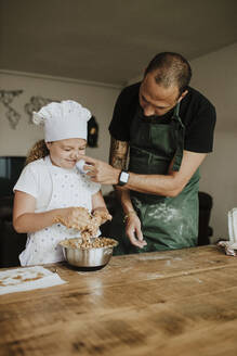 Father and daughter baking cookies at home - GMLF00424