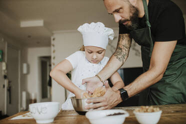 Father and daughter baking cookies at home - GMLF00430