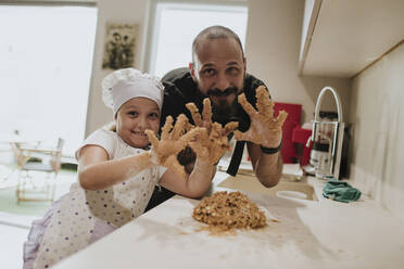Father and daughter baking cookies at home, showing their hands with dough - GMLF00433