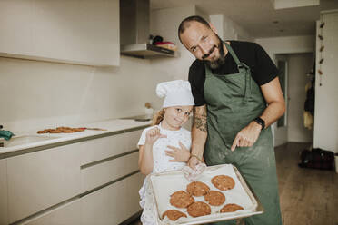 Father and daughter baking cookies at home - GMLF00436