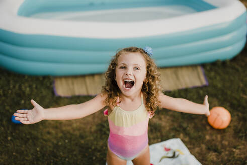 Portrait of a happy girl at inflatable swimming pool in garden - SMSF00113