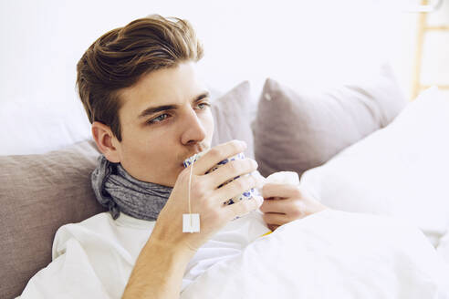 Close-up of sick young man having drink while resting on bed at home - UKOF00024