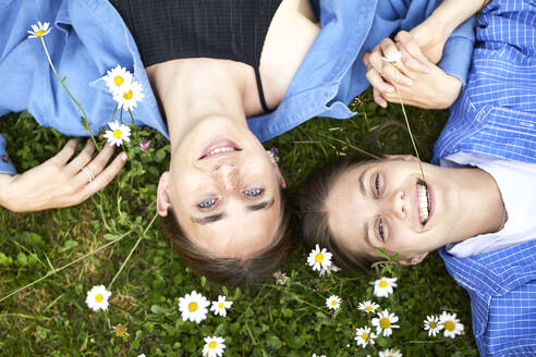 Close-up of smiling young friends lying on grassy land in garden - UKOF00060