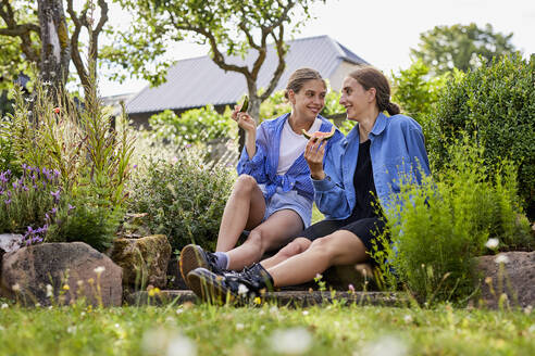 Smiling friends eating watermelon while sitting amidst plants in garden - UKOF00066