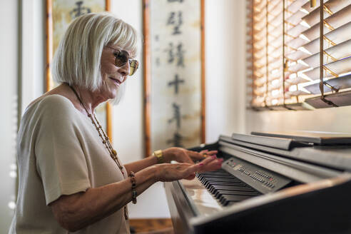 Senior woman wearing sunglasses playing piano while sitting at home - DLTSF01036