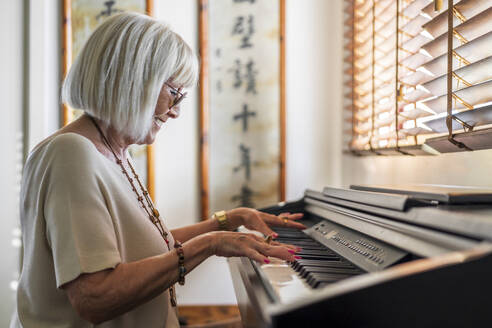 Smiling senior woman wearing sunglasses playing piano at home - DLTSF01039