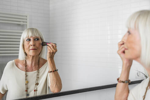 Senior woman applying make-up while looking in mirror at home - DLTSF01042