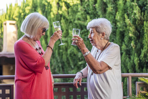 Senior female friends toasting champagne flutes while standing by railing in balcony - DLTSF01057
