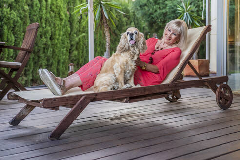 Stylish senior woman with dog relaxing on lounge chair in patio - DLTSF01066