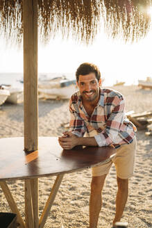 Happy mid adult man standing by table at beach during sunset - MPPF01005