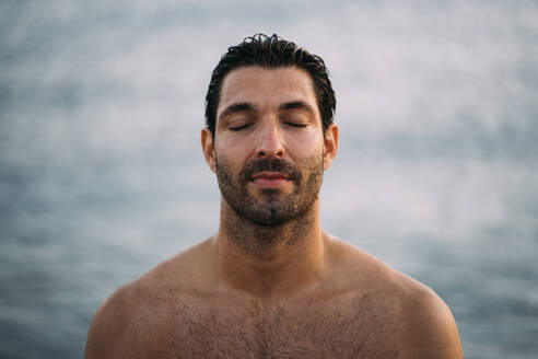 Close-up of shirtless handsome man with eyes closed against sea - MPPF01014