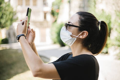 Woman wearing protective mask and taking a photo with her smartphone - XLGF00441