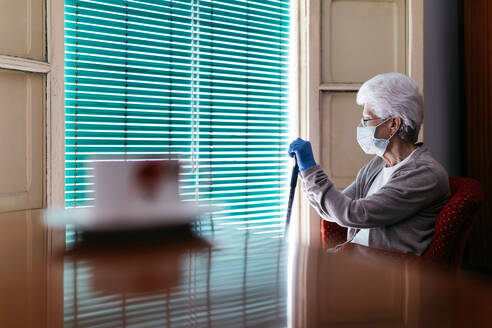 Elderly woman in protective mask and gloves with walking stick sitting near window - ADSF09693