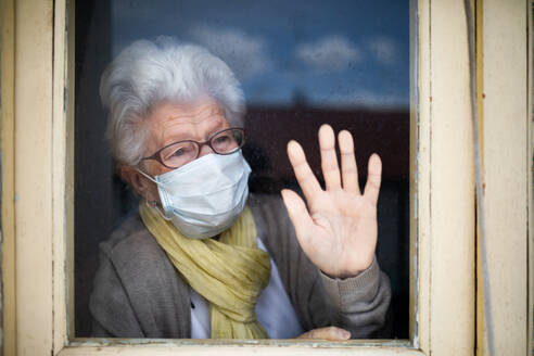 Senior woman in protective mask looking out window - ADSF09702
