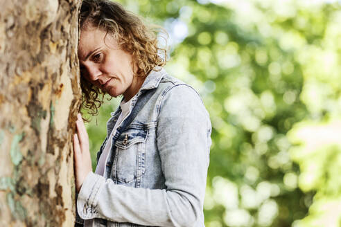Close-up of thoughtful woman leaning on tree trunk in park - JATF01231